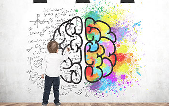 Boy writing formulas on a white wall with a brain and color splashes on it.