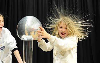 Girl touching a plasma ball causing her hair to to stand up while her mad science instructor looks on.